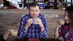 Os amigos estão sentando-se em um café e um café e um chá bebendo O indivíduo sorri, duas morenas bonitas comunica-se com o cada  vídeos de arquivo