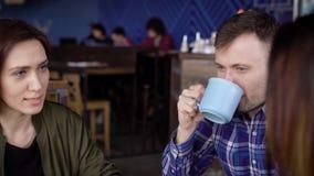 Os amigos estão sentando-se em um café e um café e um chá bebendo O indivíduo sorri, duas morenas bonitas comunica-se com o cada  video estoque