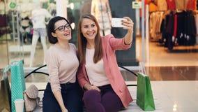 Os amigos fêmeas alegres estão tomando o selfie com o smartphone que senta-se no banco no shopping e que levanta com vidros filme
