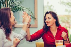 Os amigos fêmeas felizes estão dando altamente, comemorando o sucesso ao olhar-se imagens de stock