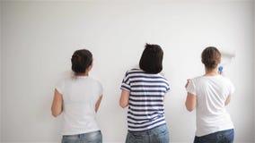 Os amigos fazem reparos em casa As meninas engraçadas dançam e pintam as paredes no plano