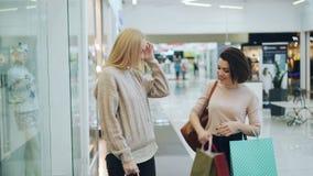 Os amigos felizes das jovens mulheres estão encontrando-se no shopping que discutem compras e que olham bens em uns sacos de pape filme