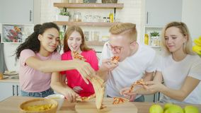 Os amigos felizes estão comendo a pizza na cozinha video estoque