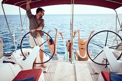 Os amigos felizes no barco apreciam junto em férias fotos de stock royalty free