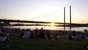 Os amigos felizes novos descansam no por do sol do banco de Rhine River, Dusseldorf, Alemanha filme