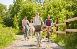 Os amigos felizes que montam engrenagem fixa bicycles no verão fotos de stock