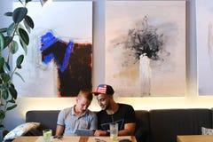 Os amigos masculinos na conversa do café discutem com a tabuleta do telefone da tecnologia Foto de Stock