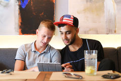 Os amigos masculinos na conversa do café discutem com a tabuleta do telefone da tecnologia Fotografia de Stock