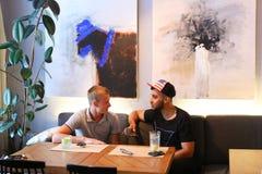 Os amigos masculinos na conversa do café discutem com a tabuleta do telefone da tecnologia Imagens de Stock Royalty Free
