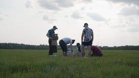 Os amigos montam um foguete tempor?rio em um campo discutem os detalhes do processo de conjunto video estoque