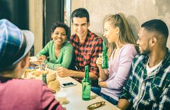Os amigos multirraciais agrupam o divertimento bebendo da cerveja e ter na barra foto de stock