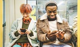 Os amigos multirraciais do moderno acoplam ter o divertimento com telefone fotos de stock royalty free