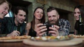 Os amigos na pizaria olham fotos no telefone e no riso filme
