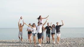 Os amigos na praia que andam, tendo o divertimento, dança, acoplam o aperto filme