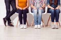 Os amigos novos alegres estão tendo um assento Foto de Stock