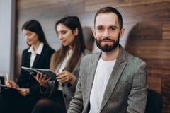 Os amigos novos diversos dos estudantes dos empresários que sentam-se junto nas cadeiras na fila que usa telefones celulares espe imagens de stock