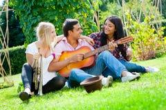 Os amigos novos jogam a guitarra e a trombeta Foto de Stock