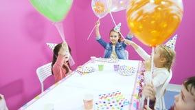 Os amigos pequenos desejam a menina bonito o feliz aniversario na sala de jogos vídeos de arquivo