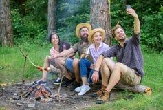 Os amigos perto da fogueira apreciam férias e o alimento roasted Homem que toma a foto perto do fundo da natureza da fogueira Os  fotos de stock