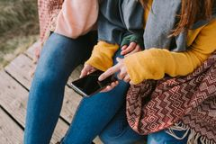 Os amigos procuram a informação no móbil que têm em suas mãos foto de stock royalty free
