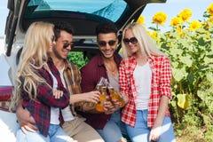 Os amigos que bebem a cerveja que brinda o tim-tim engarrafam o assento no campo exterior do tronco de carro Imagem de Stock