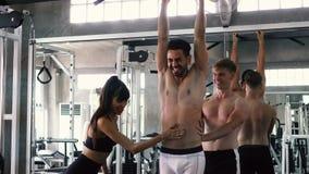 Os amigos que cheering o queixo praticando do homem levantam o exercício em barras no gym vídeos de arquivo