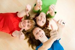 Os amigos que fazem os polegares levantam o sinal Foto de Stock