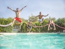 Os amigos que saltam em uma piscina imagens de stock