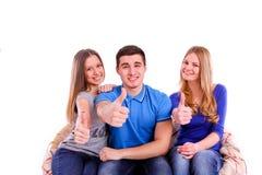 os amigos que sentam-se em um sofá e que fazem os polegares levantam s Imagem de Stock Royalty Free
