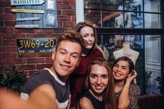 Os amigos que tomam o autorretrato fotografam, indivíduo que guarda um selfie do tiro da câmera com seus amigos fêmeas que pendur Fotografia de Stock