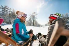 Os amigos relaxam nas cadeiras na parte superior da montanha Vista traseira Fotos de Stock Royalty Free