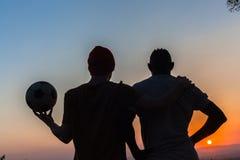 Os amigos respeitam o futebol mostrado em silhueta Fotos de Stock