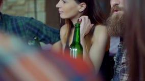 Os amigos riem, cerveja da bebida e cocktail ao ter uma boa estadia junto em uma barra video estoque