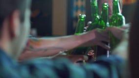 Os amigos riem, cerveja da bebida e cocktail ao ter uma boa estadia junto em uma barra vídeos de arquivo