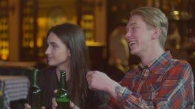 Os amigos riem, cerveja da bebida e cocktail ao ter uma boa estadia junto em uma barra Movimento lento filme