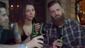 Os amigos riem, cerveja da bebida e cocktail ao ter uma boa estadia junto em uma barra Movimento lento vídeos de arquivo