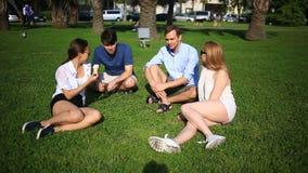 Os amigos sentam-se em uma clareira verde no meio da cidade e conversa, comem o gelado em um dia de verão quente video estoque