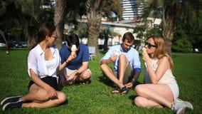 Os amigos sentam-se em uma clareira verde no meio da cidade e conversa, comem o gelado em um dia de verão quente vídeos de arquivo