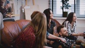 Os amigos sentam-se no sofá, filme engraçado do relógio na tevê O grupo novo caucasiano senta-se no sofá, nas bebidas e nos petis vídeos de arquivo