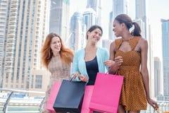 Os amigos têm o divertimento junto Menina bonita no vestido que guarda o shopp Fotografia de Stock Royalty Free