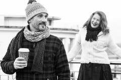 Os amores felizes dos pares bebem o café exterior O indivíduo de sorriso guarda o copo do ofício com café e escondê-lo da amiga a imagens de stock royalty free