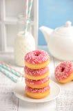 Os anéis de espuma cozidos com esmalte cor-de-rosa e polvilham Imagem de Stock