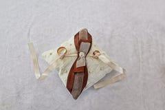 Os anéis de ouro em um laço branco pequeno descansam com as fitas brancas e marrons fotografia de stock royalty free