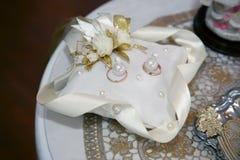 Os anéis de ouro para o casamento estão no descanso decorativo fotografia de stock