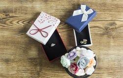 Os anéis dourados encontram-se em um vermelho e as caixas azuis com muitos abotoam rosas na tabela de madeira imagens de stock