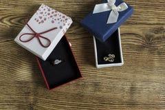 Os anéis dourados encontram-se em umas caixas vermelhas e azuis na tabela de madeira imagens de stock royalty free