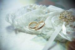 Os anéis nas flores, em uma caixa, em uma tela branca em brinquedos, cores, detalhes do casamento, alianças de casamento Imagem de Stock Royalty Free