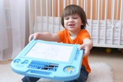 Os 2 anos agradáveis da criança mostram seu desenho na tabuleta magnética imagem de stock royalty free