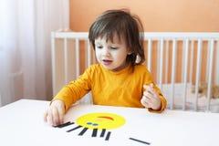 Os 2 anos bonitos da criança fizeram o applique dos detalhes de papel Imagens de Stock