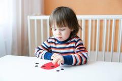 Os 2 anos bonitos da criança fizeram o joaninha de papel Foto de Stock Royalty Free